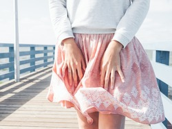 Woman stands on a pier by the sea and holds her skirt, which sways in the wind. Airy summer photo on seaside.