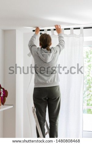 Woman stands on a stepladder near the window and hangs white curtains on the curtain rod