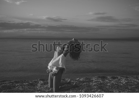 Woman stands on knees on beach in evening. Girl sexy, topless, naked breasts with wild hair at seashore at sunset. Erotic concept. Attractive young lady suntanning nude, nudist, enjoy last sun rays #1093426607