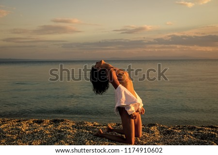 Woman stands on knees on beach in evening. Girl sexy, topless, naked breasts with wild hair at seashore at sunset. Erotic concept. Attractive young lady suntanning nude, nudist, enjoy last sun rays #1174910602
