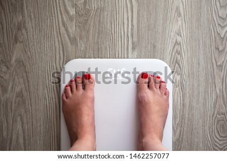 Woman stands on white modern electronic scales, which show 64.5 kg. Only feet are visible. Scales stand on gray wooden floor. Copy space. Healthy lifestyle, diet, weight loss concept. Top view.
