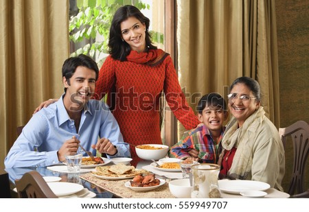 woman stands over dinner table with smiling family