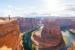 Woman Stands Over the Edge of Horseshoe Bend. Young woman enjoying view of Horseshoe bend, Arizona. Travel and adventure concept.