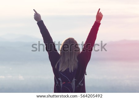 Woman Stands Victorious on Top of Mountain After Hike