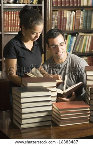 Woman stands while man sits in library. They are reading books with stacks of books on table. Vertically framed photo.