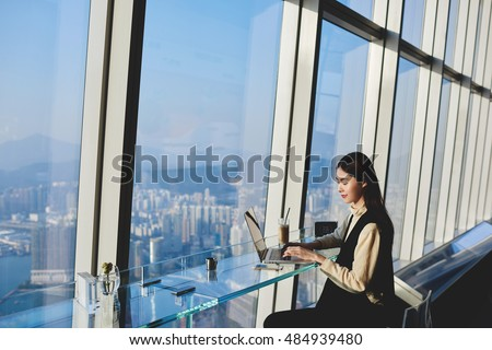 Woman start up owner of big prosperous enterprise is working on laptop computer during her business trip to China, while sitting in coffee shop in skyscraper near window with view of metropolitan city