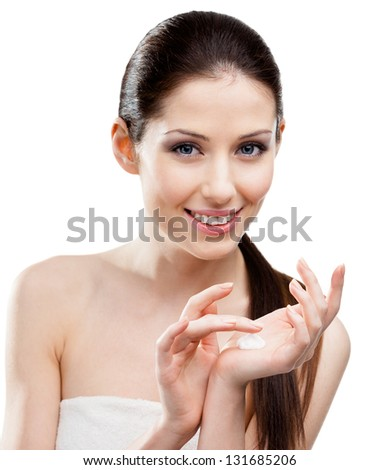 Woman starting to apply moisture cream trying it on hands, isolated on white