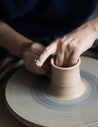 Woman starts to create a ceramic cup on the pottery wheel. Working with clay on potter's wheel, closeup of hands, crafts and arts. Anonymous hands at work. Hobby and leisure with pleasure concept.