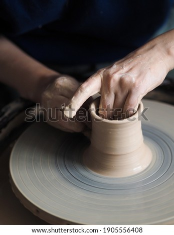 Woman starts to create a ceramic cup on the pottery wheel. Working with clay on potter's wheel, closeup of hands, crafts and arts. Anonymous hands at work. Hobby and leisure with pleasure concept. Foto stock ©