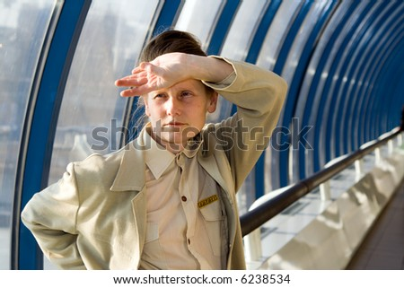 woman stay alone in passageway near floor to ceiling scenic windows and shielded her eyes from the bright light