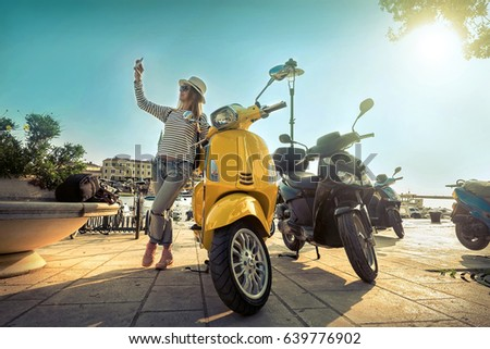 Woman stay on the evening pier with her phone and shoot selfie near the yellow scooter under sunset sky on summer day.