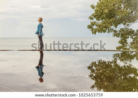 Woman staying on swimming pool with reflection on water. Sea and sky on background. Abstract portrait
