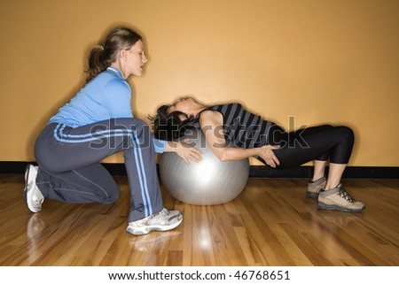 Woman steadies a balance ball for another woman lying back on it at the gym. Horizontal shot.