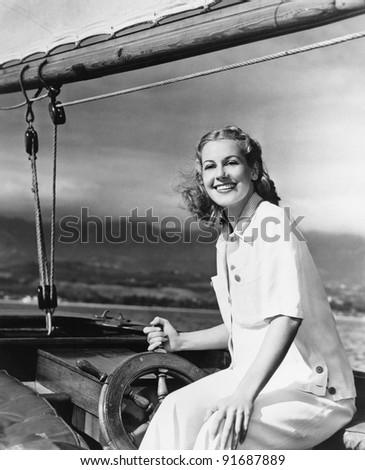Woman steering sailboat