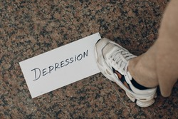 Woman step on white sheet of paper with the word Depression and foot on it.