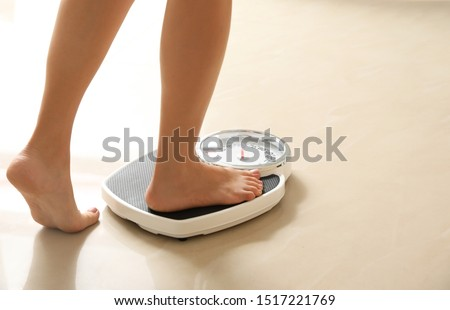 Woman stepping on floor scales indoors, space for text. Overweight problem Photo stock ©
