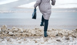 Woman steps over snow obstacles at an unclean pedestrian crossing. Pedestrian on crosswalk after strong snowfall. Pedestrian waiting to cross unclean from ice and snow road, slippery walking