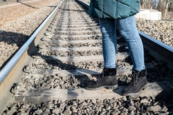 Woman steps over the rails at railway station in the city. Close up