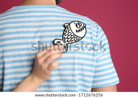 Woman sticking paper fish to friend's back on pink background. April fool's day Photo stock ©