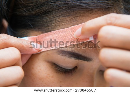 Woman sticking plaster on his head, accident