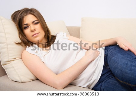 woman stomach pain.  female indoor portrait