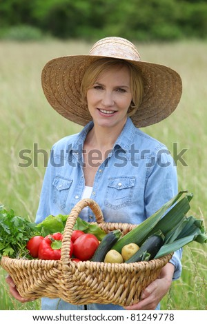 Woman stood in field carrying basket of vegetables