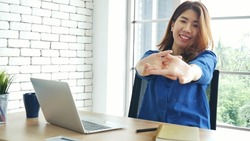 Woman streching arm raised sitting incorrect position home office desk. Back side of young asian woman tired from work body stress back pain office syndrome. Female work from home new normal concept