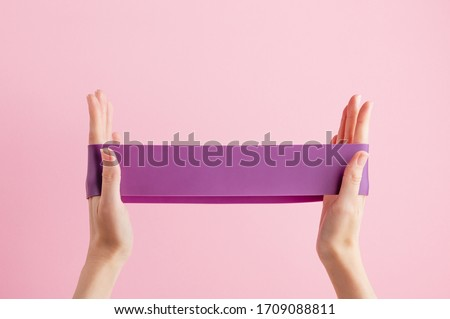 Woman stretch fitness band. Violet rubber for home exercises. Indoor and outdoor workout. Sport and healthy active lifestyle concept. Isolated on pink background