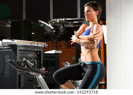 Woman stretching after workout at gym