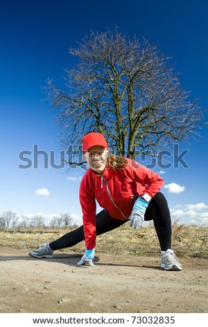 Woman stretching  and exercising on dirt country road. Running and healthy lifestyle concept. Happy female runner on outdoors exercising workout in nature.