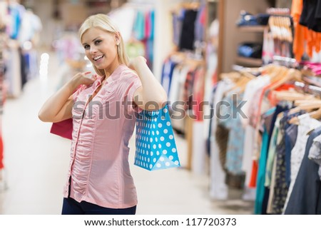 Woman stretching arms with bags
