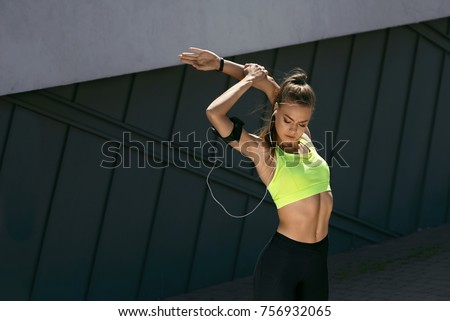 Woman Stretching Body, Doing Exercises On Street. Beautiful Athletic Girl With Fit Body In Bright Sportswear Warming Up, Doing Stretches Before Fitness Workout Outdoors. High Resolution #756932065