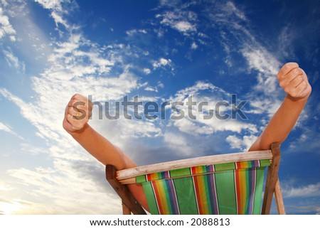Woman stretching in deckchair with sunset sky behind her