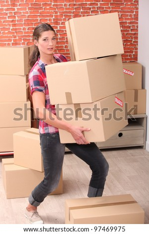 Woman struggling to carry boxes