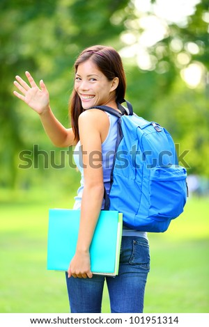 Woman student waving hello walking with school back in park smiling happy. Young female college or university student of mixed Asian / Caucasian race outside. - stock photo