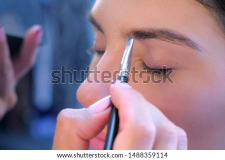 Woman stylist makeup artist making eyebrow shape form for girl, face closeup. Young woman fashion model beauty salon. Applying paint using brush. Glamour stylish fashion industry. Visagiste working.