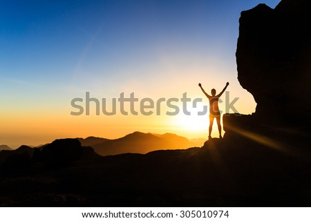 Woman successful hiking climbing silhouette in mountains, motivation and inspiration in beautiful sunset and ocean. Climber arms up outstretched on mountain top looking at inspirational landscape.
