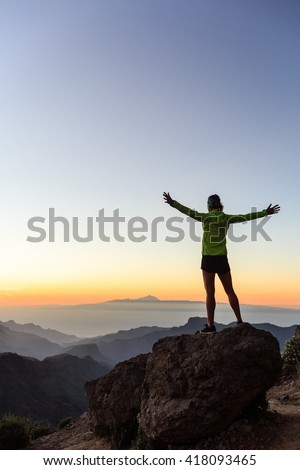 Woman successful hiking climbing silhouette in mountains, motivation and inspiration in beautiful sunset and ocean. Female hiker with arms up outstretched on mountain top looking at night landscape.