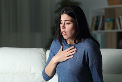Woman suffering an anxiety attack alone in the night on a couch at home