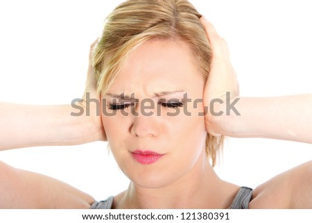 Woman suffering from a headache grimacing and holding her hands to her ears to relieve the throbbing, closeup studio head portrait on white