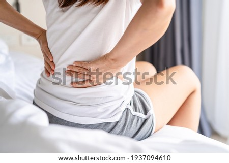Woman suffering from back ache on the bed, healthcare and problem concept Foto d'archivio ©