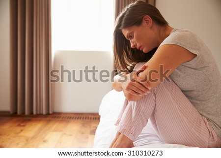Woman Suffering From Depression Sitting On Bed In Pajamas #310310273