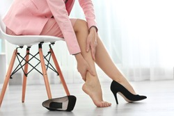 Woman suffering from leg pain in office