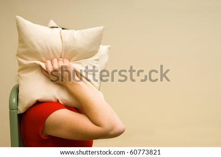 woman suffering from noise and covering her head with a pillow  irritated female lying closing ears with pillow