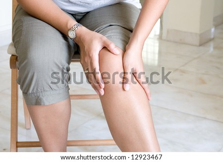 Woman suffering from pain in knee joint. - stock photo