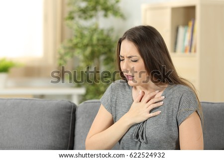 Woman suffering respiration problems sitting on a couch in the living room at home