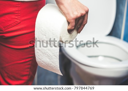 Woman suffers from diarrhea holds toilet paper roll in front of toilet bowl. Stomach upset. #797844769