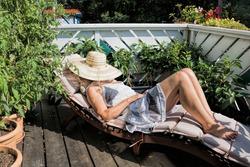 woman sunbathes on a balcony