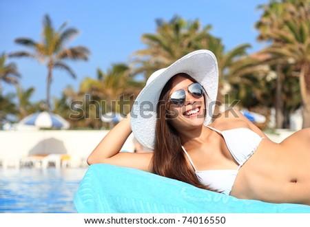 Woman sunbathing in bikini at tropical travel resort. Beautiful young Asian Caucasian woman smiling lying on sun lounger near pool.