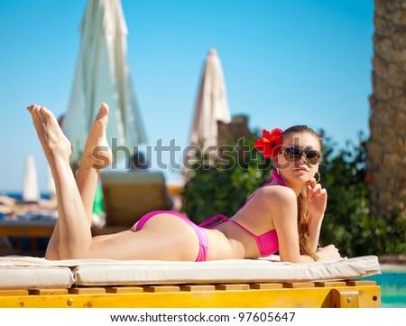 Woman sunbathing in bikini at tropical travel resort. Beautiful young woman lying on sun lounger near pool. - stock photo